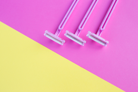 Three womens razors pink on an isolated pink and yellow background.