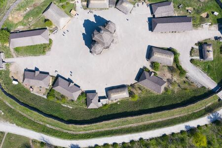 Aerial shot of an old village with wooden houses and a church. Tourist place.