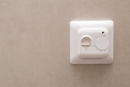 White temperature controller of a warm floor on a gray wall.