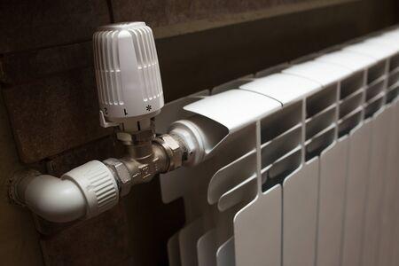 Biały grzejnik w zbliżeniu łazienki. Ogrzewanie. Wykafelkowana szara ściana.