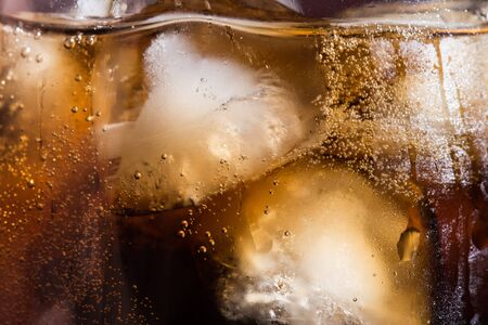 Cola texture with ice cubes in a close-up glass