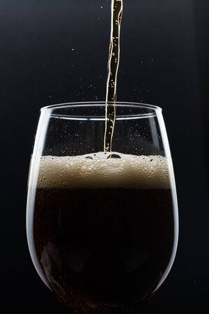 Glass of pouring fizzy drink with ice on a black background