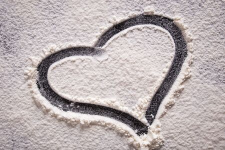 A heart shape drawn on flour on a black background. Close-up.