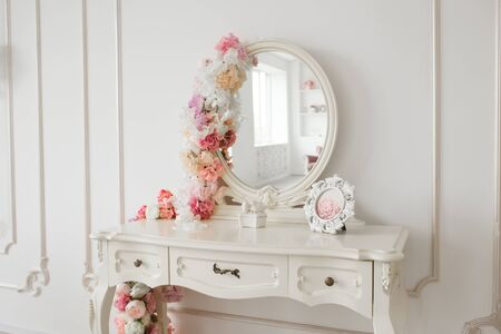 Vintage style boudoir table with round mirror and flowers. White bright room. 写真素材