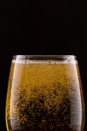 Glass with beer on a black isolated background close-up.