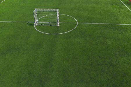 Soccer goal in the middle of a soccer field on green grass.