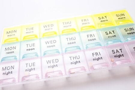 Organizer for medical pills on a white isolated background close-up. Organization of taking pills of the day.
