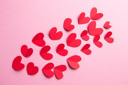 A lot of small hearts of red color against on a pink background. Happy Valentines Day.