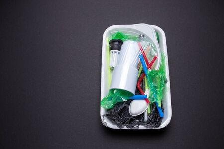 Set of plastic waste in a packed tray on a black isolated background. The problem of ecology and environmental pollution.