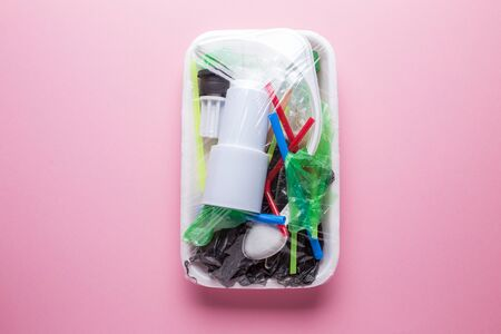 Set of plastic waste in a packed tray on a pink isolated background. The problem of ecology and environmental pollution.