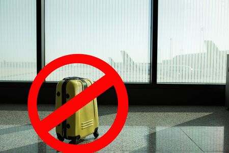 Suitcases in airport departure lounge, airplane in background, summer vacation concept, traveler suitcases in airport terminal waiting area, empty hall interior with large windows.