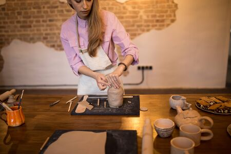 Girl sculpts a jug of clay in a pottery.