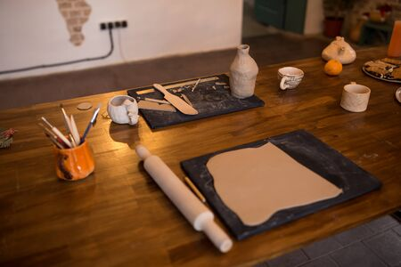 A master class in modeling a clay jug. Table with clay and a tool for creativity. Zdjęcie Seryjne