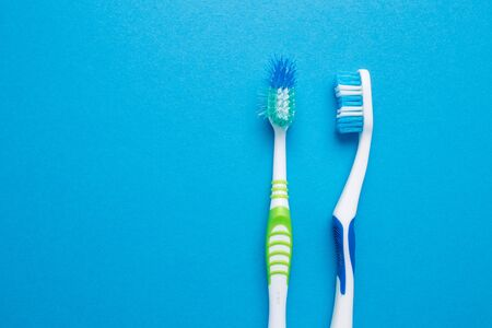 Used old and new toothbrush on a blue background.