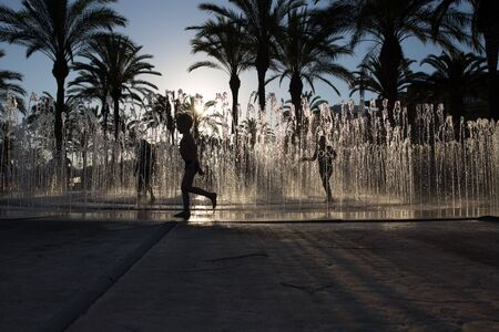 silhouette of a group of children playing in a water fountain