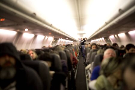 Blurred interior of an airplane with passengers.