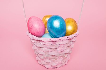 Multi-colored Easter eggs in a basket on a pink isolated background. Easter is a bright holiday. Zdjęcie Seryjne
