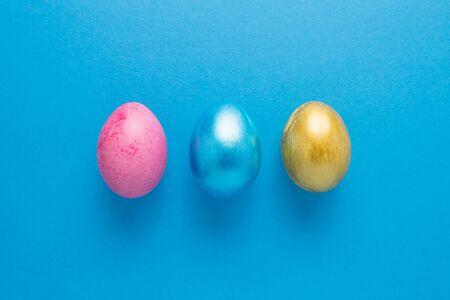 Multi-colored Easter eggs on a blue isolated background. Easter is a bright holiday. Zdjęcie Seryjne