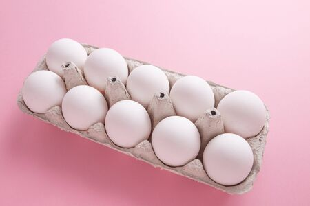 Chicken eggs in a tray close-up on a pink background.