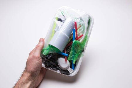 Male hand holds a tray with plastic waste on a white isolated background. The problem of ecology and environmental pollution. Zdjęcie Seryjne