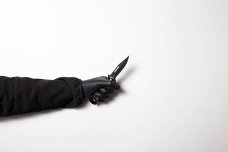 Male hand in a black jacket on a white background with a knife.