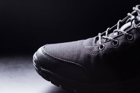 Black mens sneakers close-up on a black isolated background. Zdjęcie Seryjne