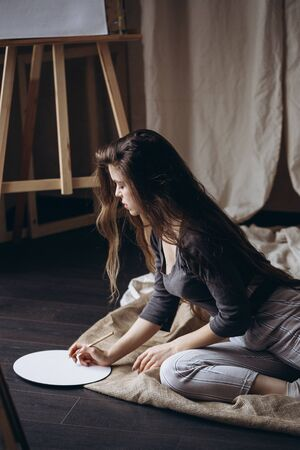Brunette girl sitting on the floor draws with a brush
