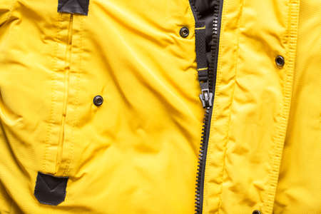 Zipper on clothes close-up. black color. Bright yellow jacket