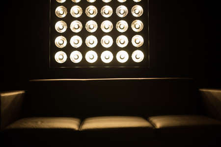 Brown sofa in a dark room. Light falls behind a stand with light bulbs. Zdjęcie Seryjne