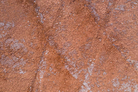 The texture of dry earth is red. View from above.