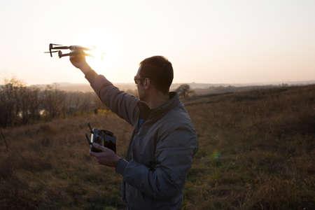 A man launches a drone into the sky. Drone operator with setting sun. Archivio Fotografico