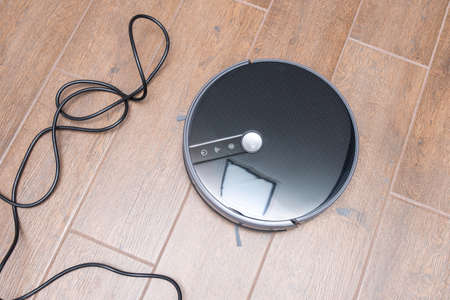 Robot vacuum cleaner on a brown floor. Obstacle in the form of wires. The robot vacuum cleaner is entangled in the wires.