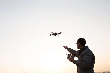 A man launches a drone into the sky. Drone operator with setting sun. Фото со стока
