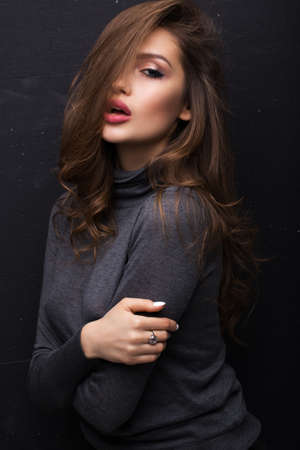 Portrait of a beautiful girl in a gray sweater on a black background