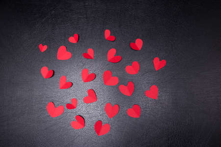 A lot of small hearts of red color against on a black background. Happy Valentines Day.