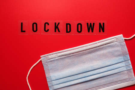The word lockdown and a medical mask on a red background. Second wave covid 19. 写真素材