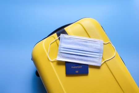 Yellow suitcase and a medical mask on a blue background. Safe travel concept.