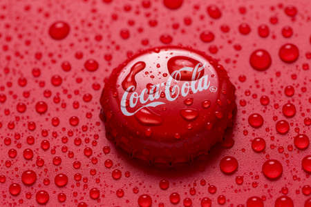 Kiev, UKRAINE - January 28, 2019: classic cap close-up of Coca-cola. Cap of cola on a red background with water drops.