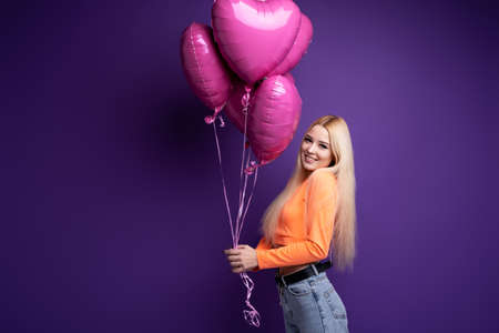 Happy blonde with heart-shaped balloons on a purple background in the studio.