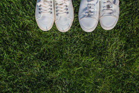 Womens and mens white sneakers on green grass. The guy and the girl are facing each other. View from above.