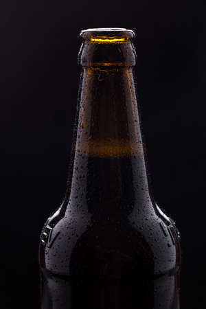 Bottle of beer with drops of water close-up on a black isolated background.