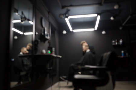 Blurred photo of a barber shop room in black style and lamps. Фото со стока