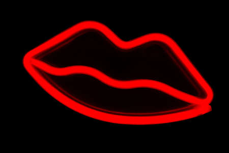 Blurry neon red lips close-up on a black isolated background.
