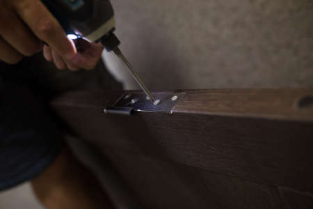 Drilling a hole in the furniture to install a lock on the door close-up.