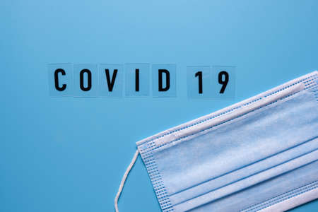The word COVID19 medical mask on a blue background top view.