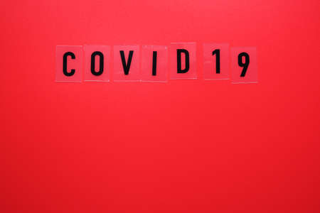 The word covid 19 on a red background close-up.