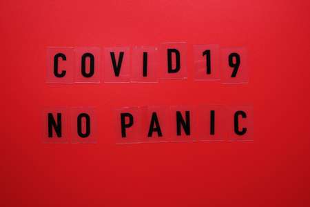 Words covid 19 no panic on a red background and a medical mask. Фото со стока