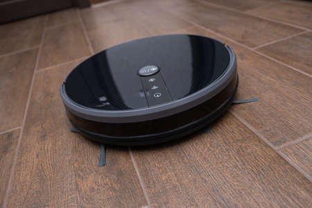 Robot vacuum cleaner on a brown laminate close-up.