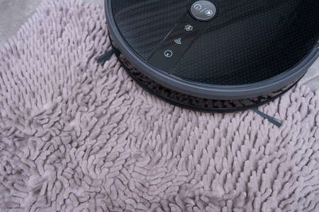Robot vacuum cleaner on a gray carpet with a large pile close-up.