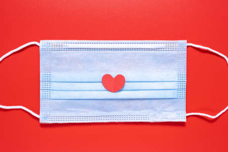 Medical mask with a heart on a red background. Valentines Day.